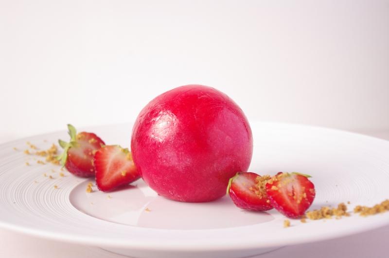 Sphère en sucre garnie de fraises, crumble et crème au Philadelphia