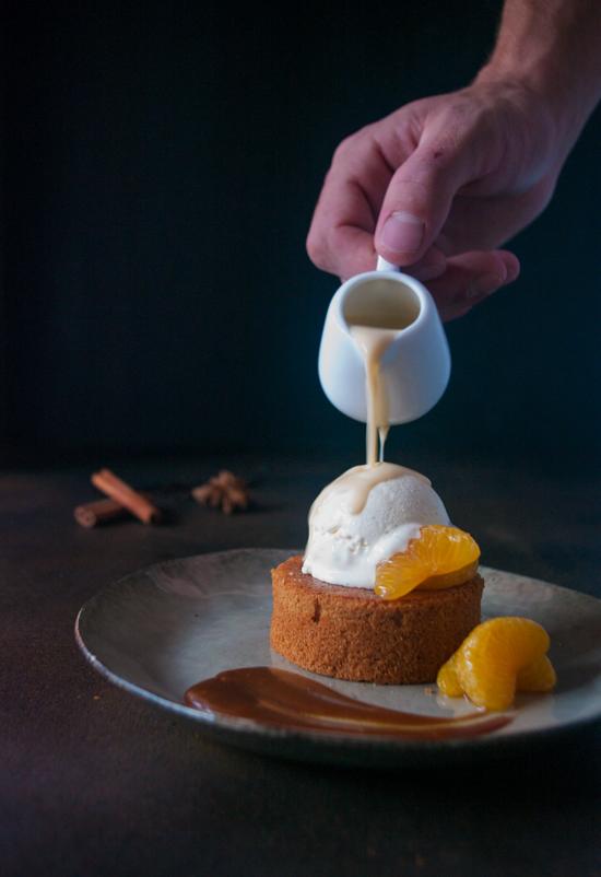 Un gâteau moelleux aux agrumes, des clémentines poêlées, de la glace vanille et une crème anglaise aux agrumes et aux épices.