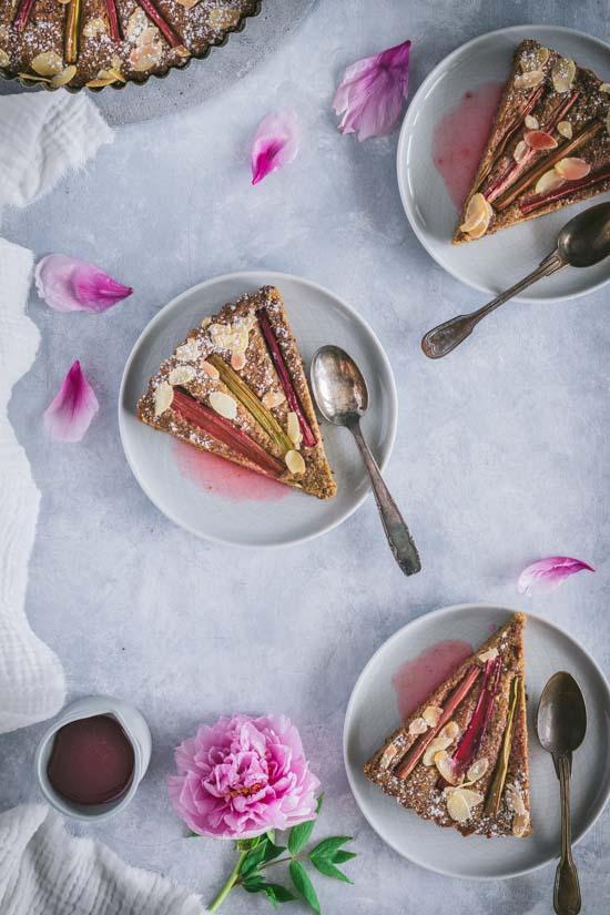 Parts de financier à la rhubarbe servies avec le sirop fraise rhubarbe