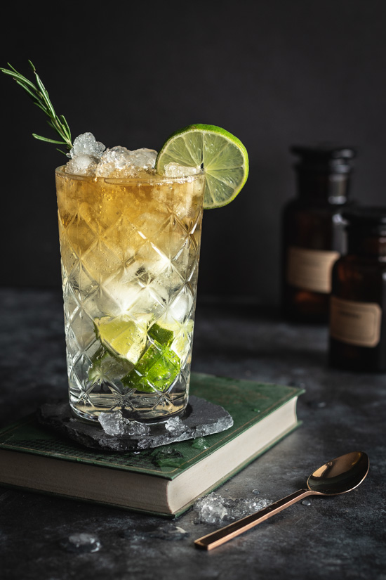 Un cocktail à base de rhum épicé dans un grand verre avec plein de citron vert