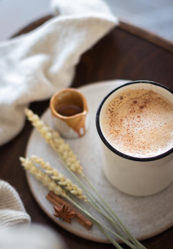 Une tasse de latte à la pomme et au caramel avec un petit pot de caramel