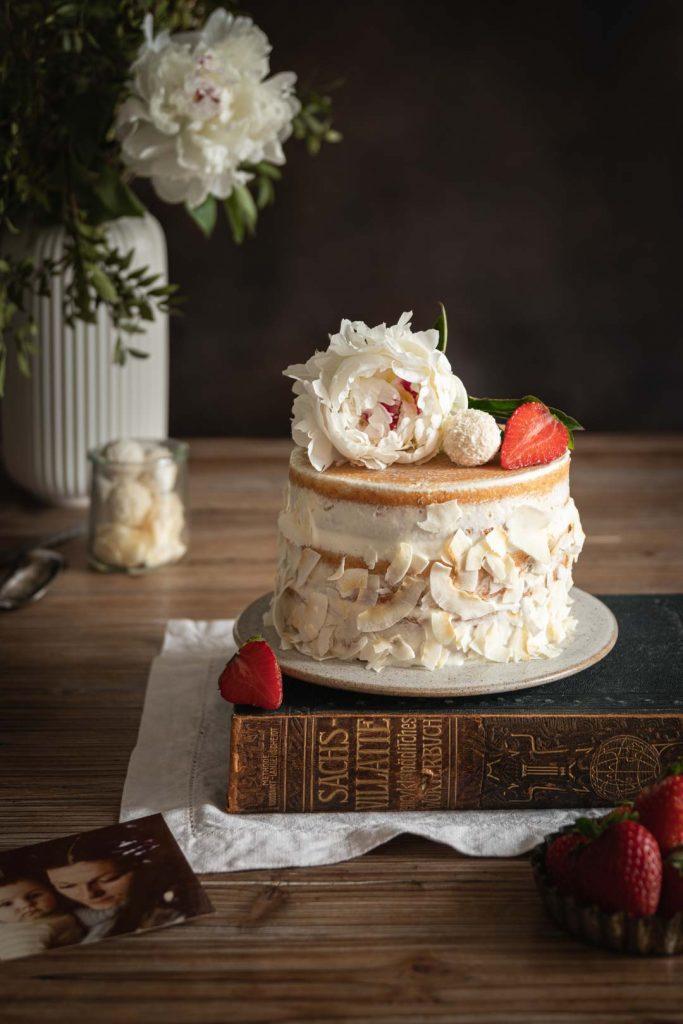 Naked cake à la noix de coco fourré de fraises posé sur un livre ancien