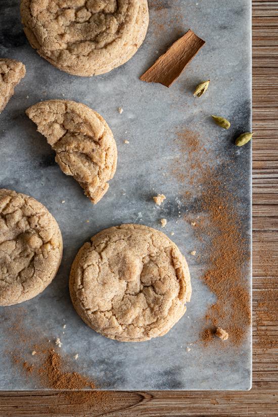 Des cookies et des épices sont disposés sur une plaque en marbre